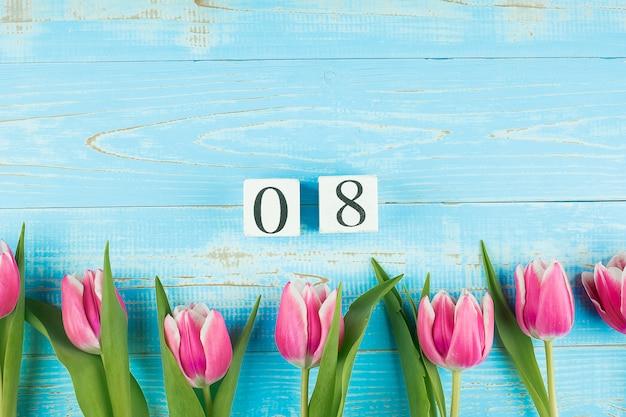 Roze tulpenbloem en 8 maart-kalender op blauwe houten lijstachtergrond met exemplaarruimte voor tekst. liefde, gelijke en internationale vrouwendag concept