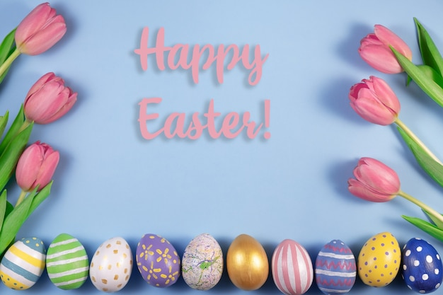 Roze tulpenbloemen en kleurrijke eieren die op blauw worden geïsoleerd