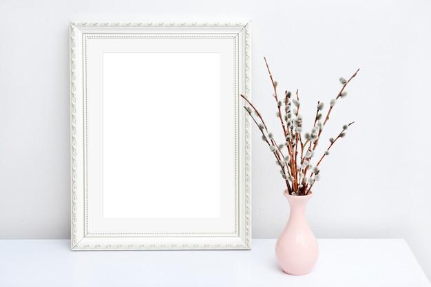 Roze vaas met wilg en witte frame met kopie ruimte op een witte tafel