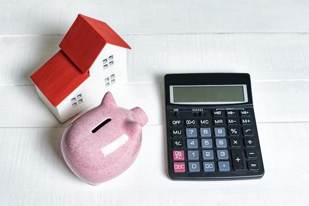 Roze varkensspaarvarken, rekenmachine en broodplankmodel van een huis met een rood dak op een lichte achtergrond.