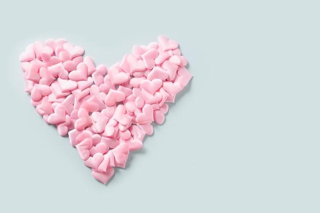 Roze vele harten in vorm in groot hart op blauwe achtergrond. valentijnsdag wenskaart met kopie ruimte. liefde concept.