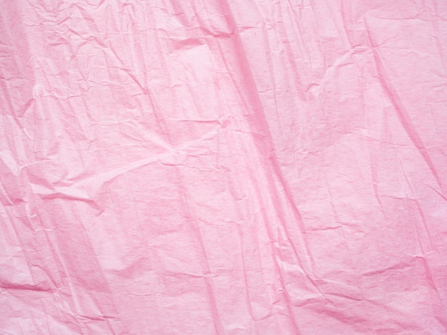 Roze verfrommeld papier textuur achtergrond. macro-opname van inpakpapier. gevouwen bladachtergrond. geweven effect van pagina. abstract patroon, roze achtergrond oppervlak. gerimpelde textuur van blad