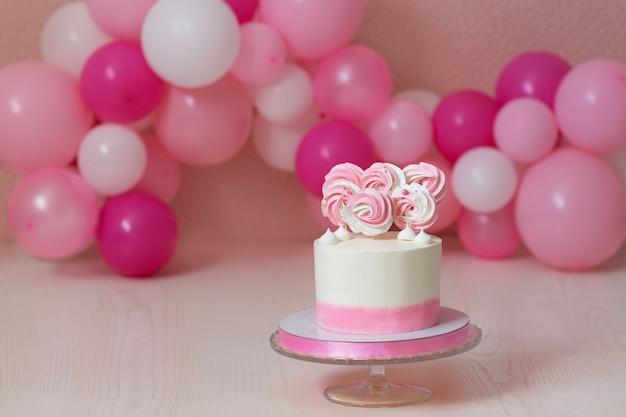 Roze verjaardagstaart en ballonnen