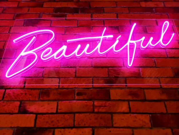 Roze verlichte gloeiende mooie tekst op bakstenen muur