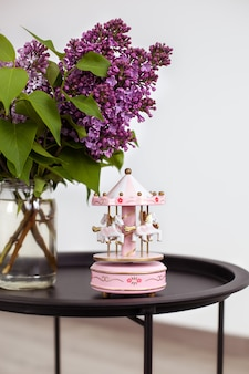 Roze vintage muzikale carrousel en boeket van prachtige lila lentebloemen in vaas op vintage salontafel.