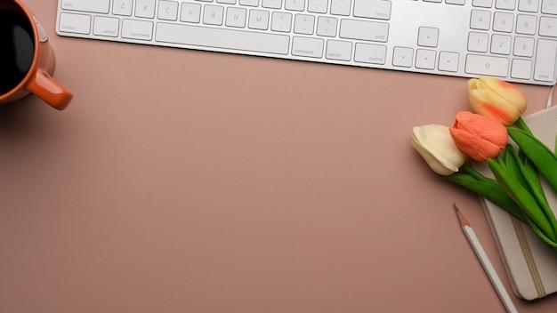 Roze vrouwelijke creatieve plat lag werkruimte met computertoetsenbord, tulp bloemen en kopie ruimte, bovenaanzicht