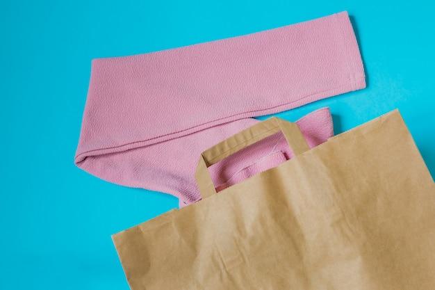 Roze vrouwenblouse in papier ambachtelijk pakket op blauw.