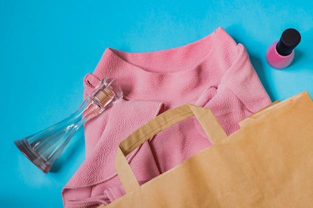 Roze vrouwenblouse, nagellak en parfums in papieren handwerkpakket op blauw.