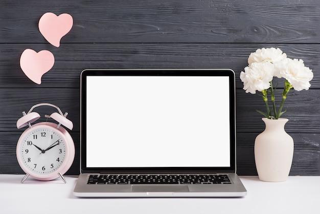 Roze wekker en bloemenvaas op wit bureau tegen houten behang