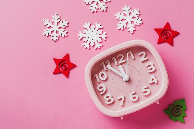 Roze wekker met speelgoed en sneeuwvlokken die op roze oppervlakteachtergrond liggen. nieuwjaar of kerstmis concept. bovenaanzicht. omgaan met ruimte.