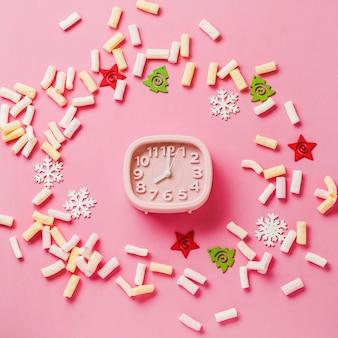 Roze wekker met speelgoed en sneeuwvlokken liggend op roze oppervlak. nieuwjaar of kerstmis concept. bovenaanzicht. omgaan met ruimte.vierkante afbeelding.