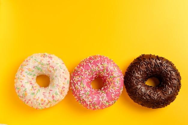 Roze witte en zwarte chocolade donuts op gele achtergrond