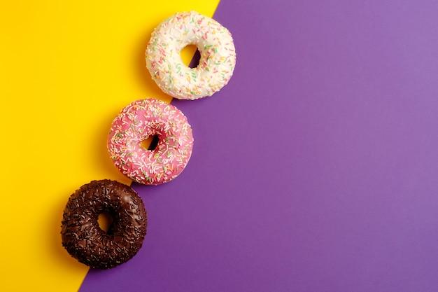 Roze witte zwarte chocolade donuts op gele en violette diep paarse achtergrond