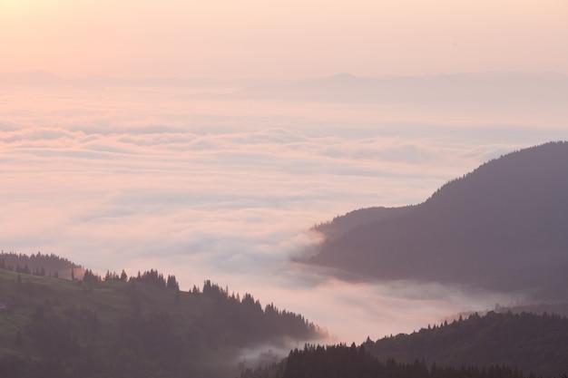 Roze wolken boven de bergen in de ochtend