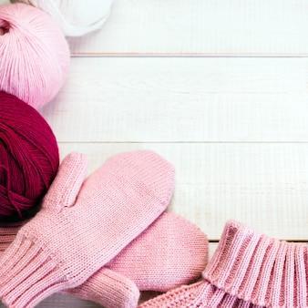 Roze wollen wanten op een witte houten tafel
