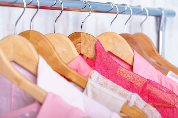 Roze womens kleding op houten hangers op rek in een modewinkel. . kast vrouwen jurken, blouses close-up