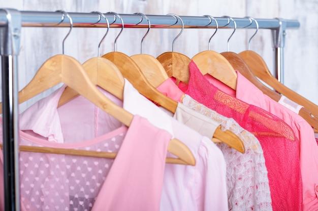 Roze womens kleding op houten hangers op rek in een modewinkel. kast vrouwen jurken, blouses