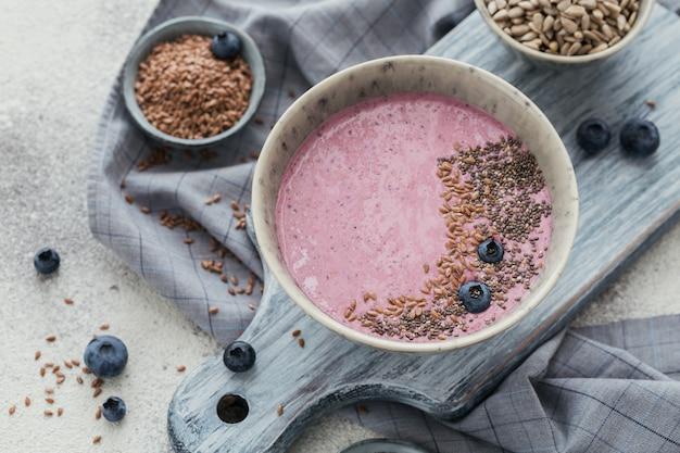 Roze yoghurt-smoothiekom gemaakt met verse bosbessen en zaden. gezond voedselconcept. detailopname