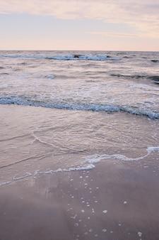 Roze zandstrand. kustlandschap met mooi zandstrand. golven uitzicht