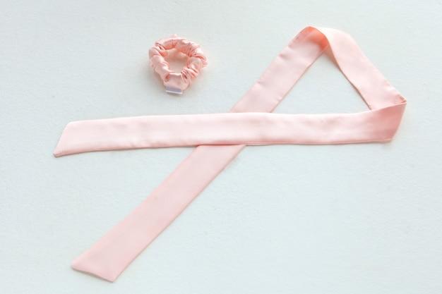 Roze zijde scrunchy geïsoleerd op wit. platliggende kappersgereedschappen en accessoires als kleur haar scrunchies, elastische haarbanden, bobble sports scrunchie haarband