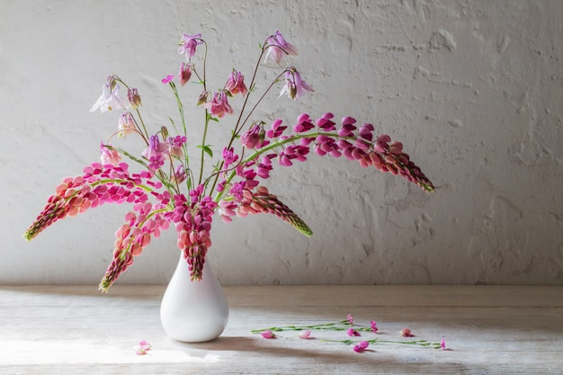 Roze zomerbloemen in witte vaas op wit oud