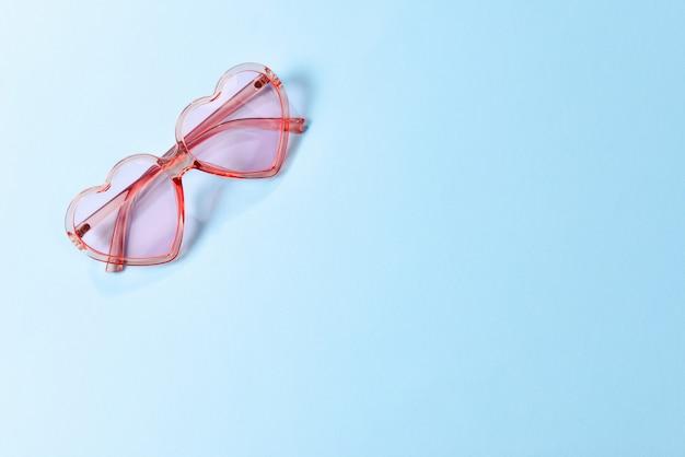 Roze zonnebril op een blauwe achtergrond. ruimte voor tekst of ontwerp.
