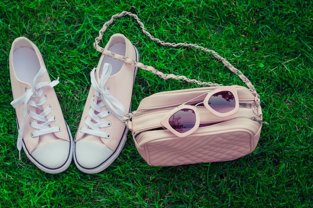 Roze zonnebril op een roze tas en sneakers met groen gras als achtergrond