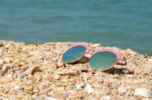 Roze zonnebril tegen de zon op het strandzand