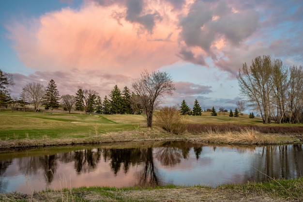 Roze zonsondergangwolk over swift current creek op een golfbaan in swift current, sk, canada