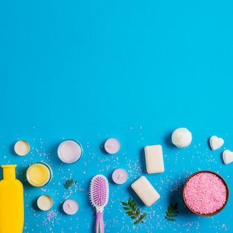 Roze zout; zeep; crème en shampoo met verschillende soorten kaarsen op blauwe achtergrond