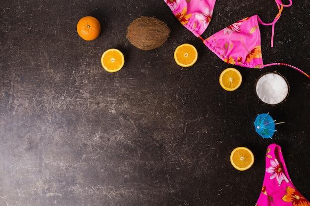 Roze zwembroek, kokosnoot, sinaasappel, cocktailparaplu's op een donkere marmeren achtergrond. zomer concept