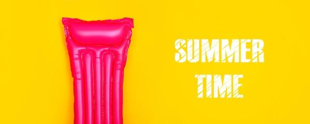 Roze zwemmatras op een gele achtergrond, concept van zomertijd op zee, panoramisch beeld