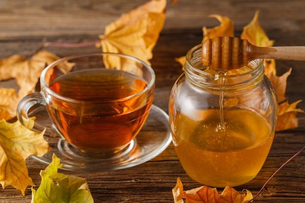Rozebottelthee in transparante beker en theepot met honing en herfstbladeren. warme herfstdrank