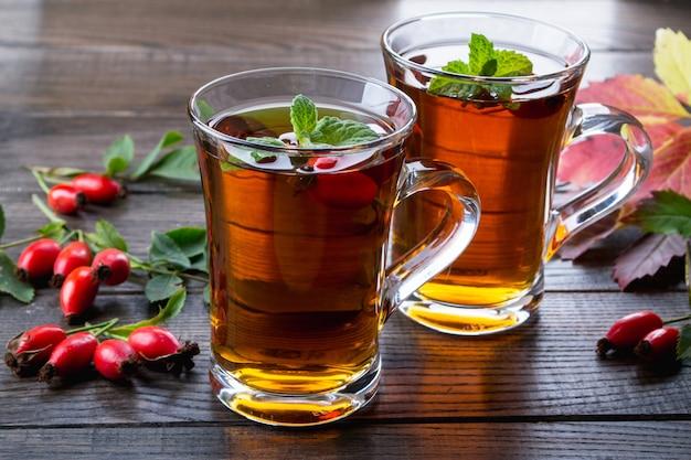 Rozebottelthee in transparante beker met honing en verse bessen. vitamine c drankje op donkere tafel