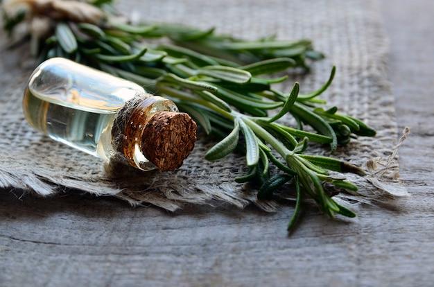 Rozemarijn etherische olie in een glazen fles en rozemarijnbladeren
