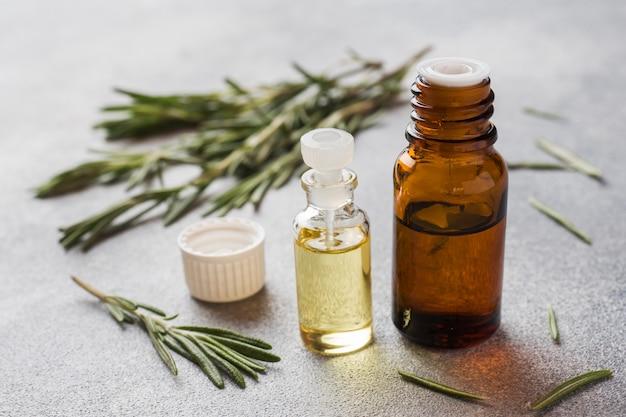 Rozemarijn etherische olie in een glazen fles met verse tak rozemarijn kruid op grijze tafel voor spa, aromatherapie en lichaamsverzorging. ruimte kopiëren.