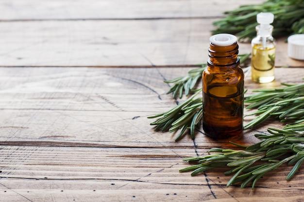 Rozemarijn etherische olie in een glazen fles met verse tak rozemarijn kruid op houten tafel voor spa, aromatherapie en lichaamsverzorging. ruimte kopiëren.