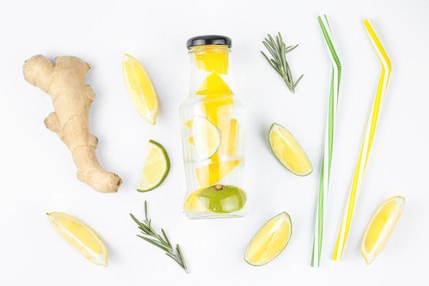 Rozemarijn gember limoen cocktail stro fles vers. gezond verfrissend drankje. gezonde voedselsamenstelling die op witte muur wordt geïsoleerd. tonic ingrediënten.