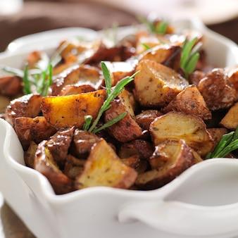 Rozemarijn kruid aardappelen in witte ovenschaal close-up