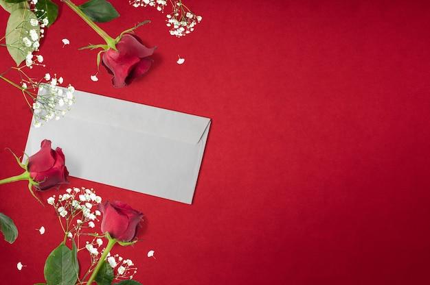 Rozen achtergrond met liefdesbrief en witte decoratieve bloemen met kopie ruimte, plat lag, bovenaanzicht