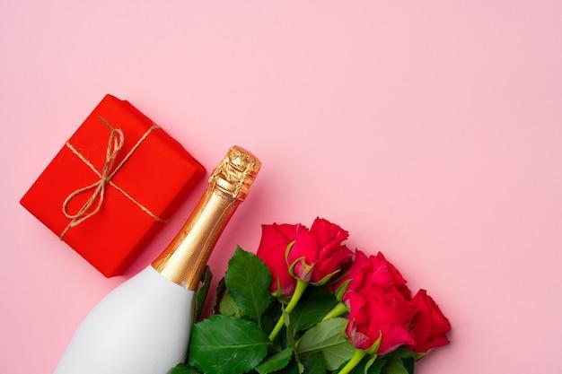 Rozen boeket, fles champagne en geschenkdoos plat lag bovenaanzicht