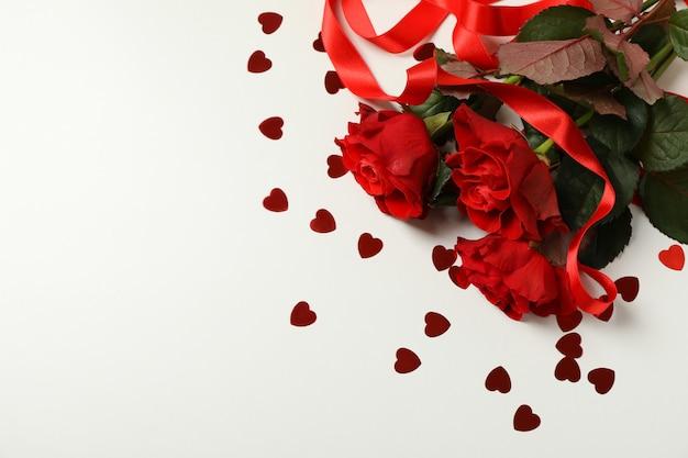 Rozen, decoratieve harten en en lint op witte achtergrond