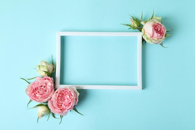 Rozen en leeg frame op blauwe achtergrond