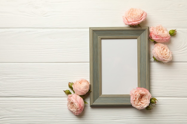 Rozen en leeg frame op witte houten achtergrond