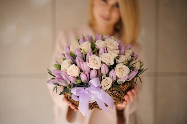 Rozen en tulpen in de mand in handen van het meisje
