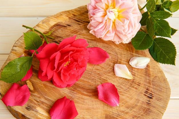 Rozen en verspreide bloemblaadjes op een standaard gemaakt van gesneden hout.