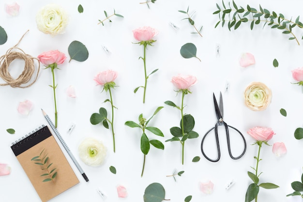 Rozen, eucalyptusbladeren, takken, notitieboekje, schaar
