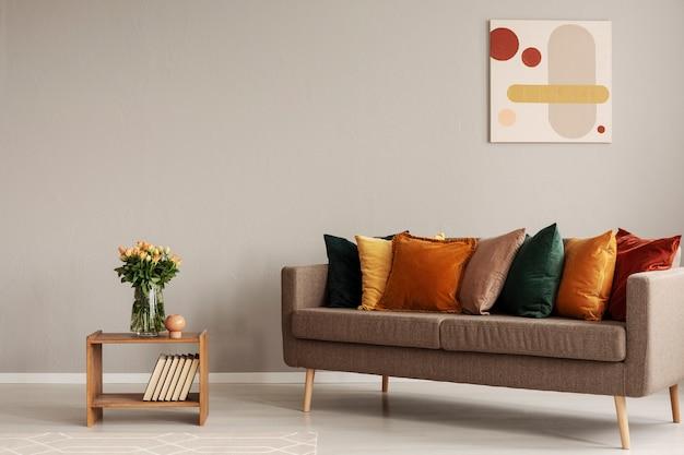 Rozen in glazen vaas op houten plank met boeken naast comfortabele bank met oranje, gele, beige en smaragdgroene kussens