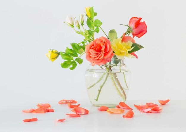 Rozen in glazen vaas op witte muur