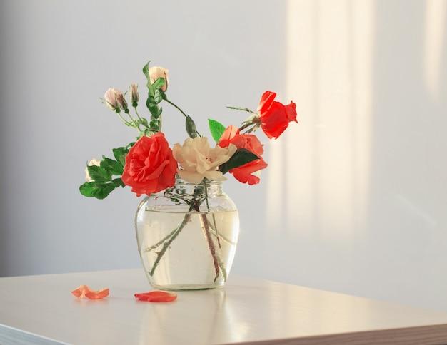 Rozen in glazen vaas op witte tafel